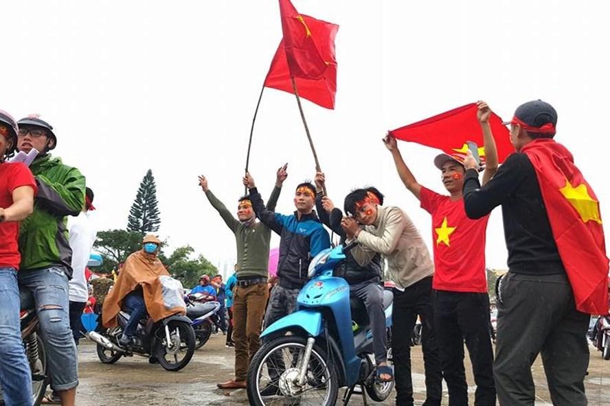 Người dân TP.Đồng Hới (Quảng Bình) đội mưa trong sắc đỏ sao vàng cổ vũ đội tuyển U23 Việt Nam chiều 27.1. Ảnh: Lê Phi Long