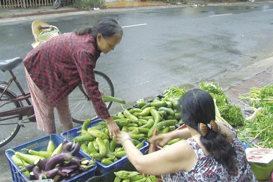 Người lao động nghèo nhận rau củ miễn phí tại quầy. Ảnh: THANH THANH