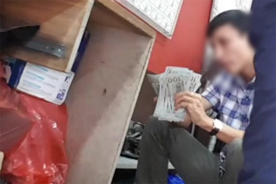 Nam thanh niên đếm lại số ngoại tệ vừa giao dịch tại một cửa hàng trên phố Hà Trung.