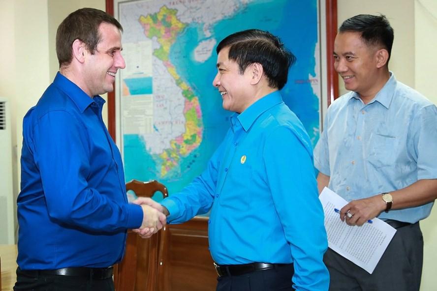 Chủ tịch Tổng LĐLĐVN Bùi Văn Cường (phải) bắt tay đón tiếp Tổng Thư kí Hội đồng Công đoàn New Zealand Sam Huggard tại trụ sở Tổng LĐLĐVN.