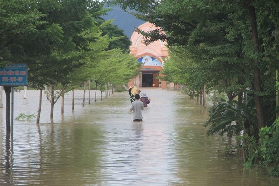 Người dân xã Tân Hải, huyện Ninh Hải, Ninh Thuận đi lại trong biển nước để tiếp tế lương thực cho người thân. Ảnh: Thắng Nam