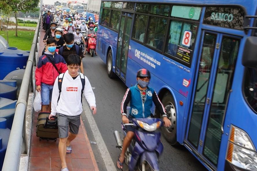 """Đường ùn tắc, nhiều hành khách ở TPHCM về quê ăn Tết sợ trễ chuyến phải xuống xe """"cuốc bộ"""" ra bến xe Miền Đông. Ảnh: Minh Quân"""