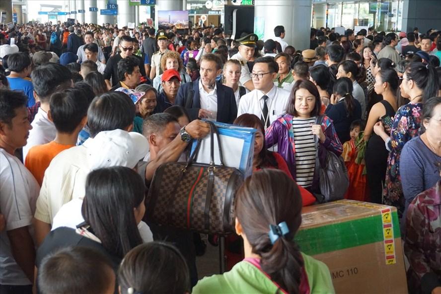 Sảnh ga quốc tế sân bay Tân Sơn Nhất chật kín lượng người đến đón người thân về nước ăn tết. Ảnh: MINH QUÂN