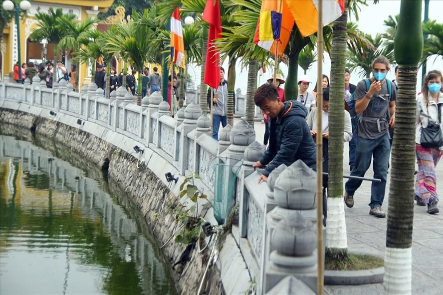 Một nhóm người ngang nhiên bắt cá vừa được phóng sinh trước cửa Phật.