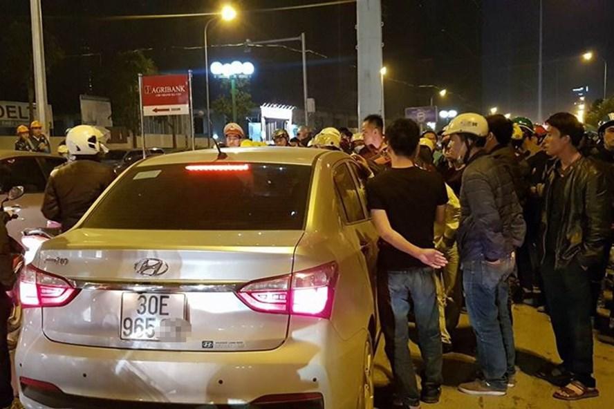 Hàng trăm người vây quanh chiếc ô tô có tài xế đang cố thủ trong xe.