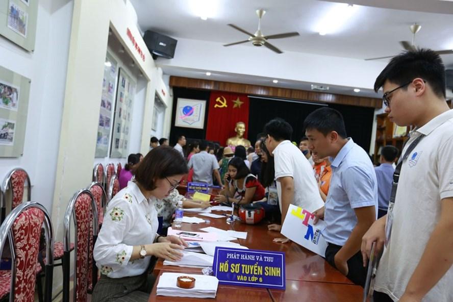 Phụ huynh làm thủ tục tuyển sinh vào lớp 6 tại một trường THCS trên địa bàn quận Cầu Giấy (Hà Nội). Ảnh: HẢI NGUYỄN