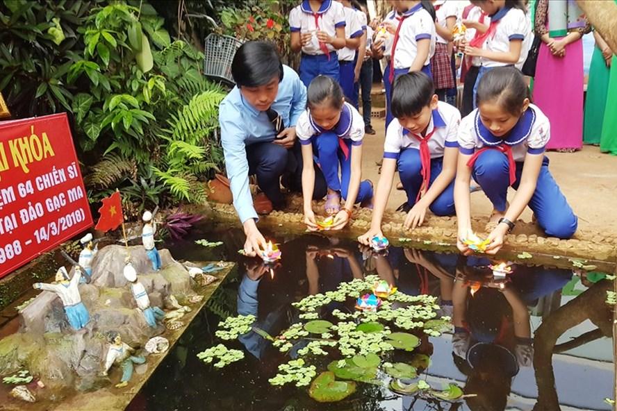 Thầy Hiệu trưởng và các em học sinh trường Tiểu học Hướng Phùng thả hoa đăng tưởng niệm 64 anh hùng liệt sĩ hi sinh trong trận Gạc Ma. Ảnh: PV
