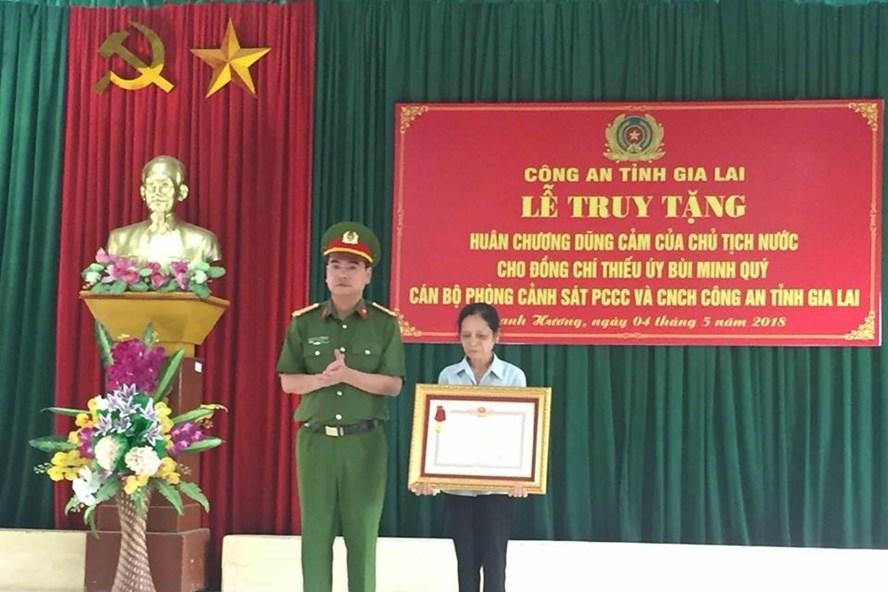 Người thân lên nhận phần thưởng cao quý mà nhà nước truy tặng thiếu úy Bùi Minh Qúy. ảnh: Quang Huy