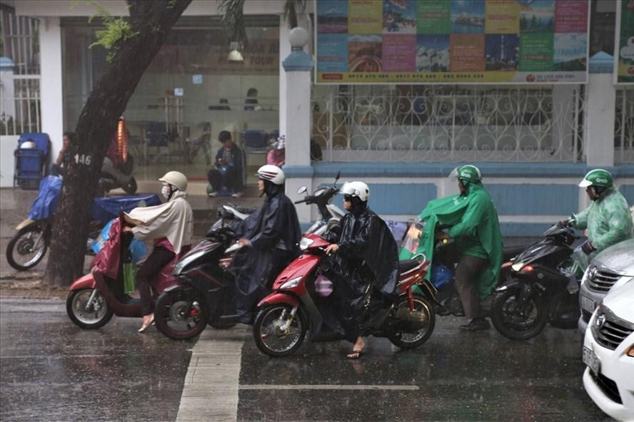 Người dân TPHCM co mình dưới trận mưa lớn ngay đầu giờ chiều hôm nay. Ảnh: Trường Sơn