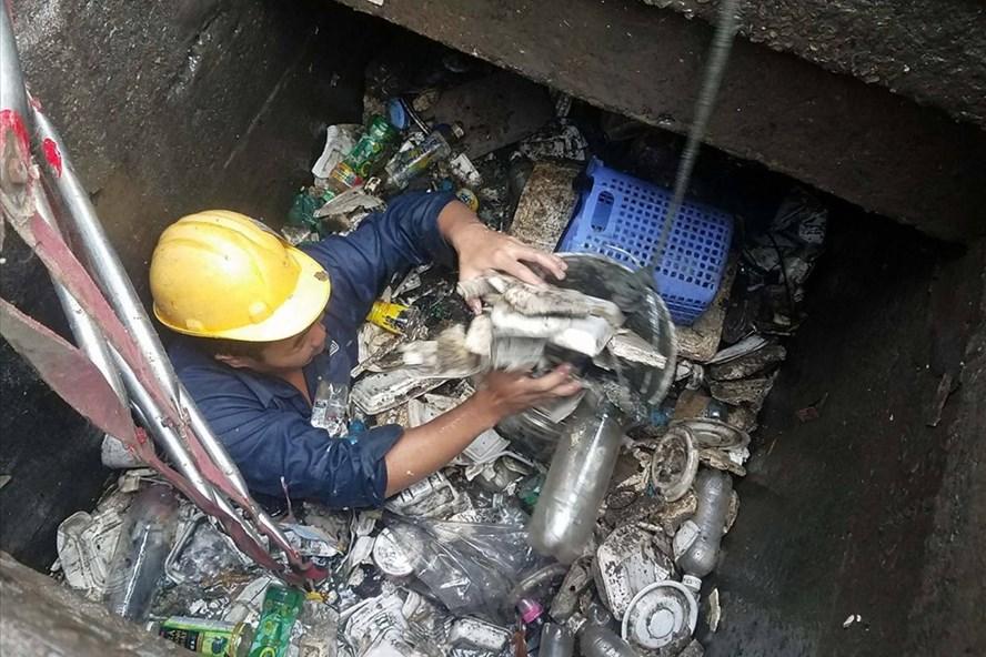 Công nhân ngâm mình vớt rác dưới cống.  Ảnh: N.B