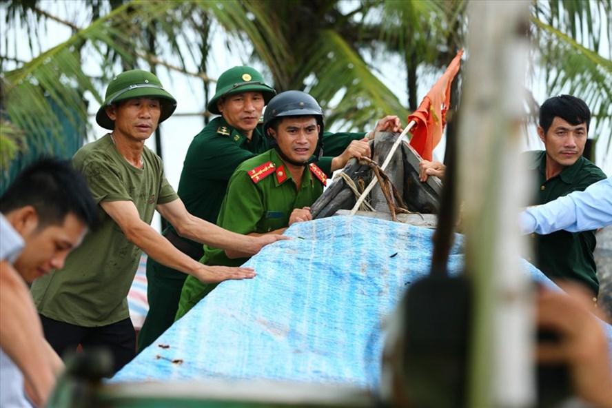 Lực lượng biên phòng và công an cùng ngư dân khẩn trương chằng buộc tàu, thuyền sát lại với nhau để tránh gây hư hỏng.