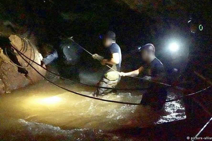 Các thợ lặn đặc nhiệm SEAL đánh giá mực nước tại một khoang ngầm trong hang.