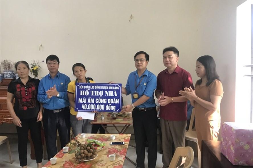 Ông Trịnh Văn Bừng, Tỉnh ủy viên, Chủ tịch LĐLĐ tỉnh Hà Nam (thứ 2 từ trái sang) trao hỗ trợ nhà Mái ấm CĐ tới chị Nguyễn Thị Huệ. Ảnh: PV