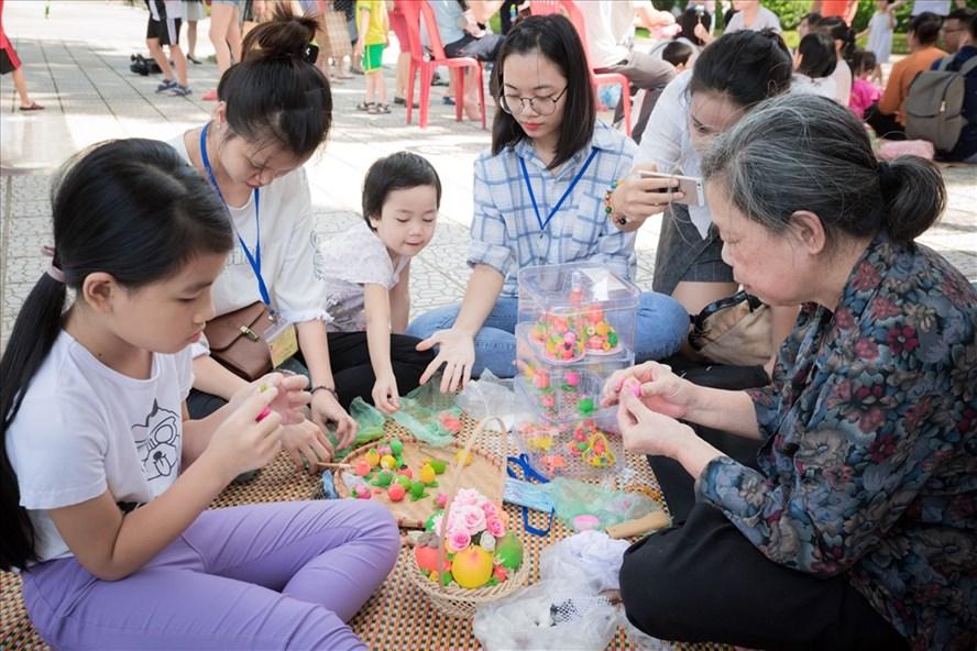 Nghệ nhân dạy các em nhỏ làm hoa quả bằng bột. Ảnh: T.L