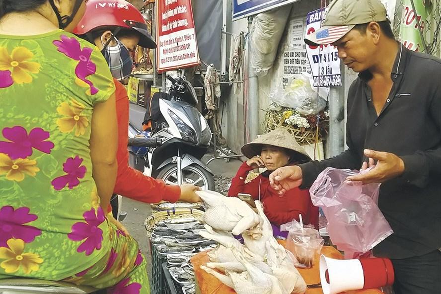 Người dân mua gà không đầu tại chợ tự phát bên hông chợ Bình Triệu (quận Thủ Đức, TPHCM). Ảnh: MINH QUÂN