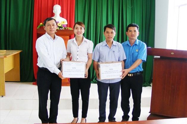 Chủ tịch LĐLĐ tỉnh Đắc Nông Đinh Trọng Nhương (ngoài cùng bên trái) trao vở đến cho các em học sinh. Ảnh: Quang Hùng