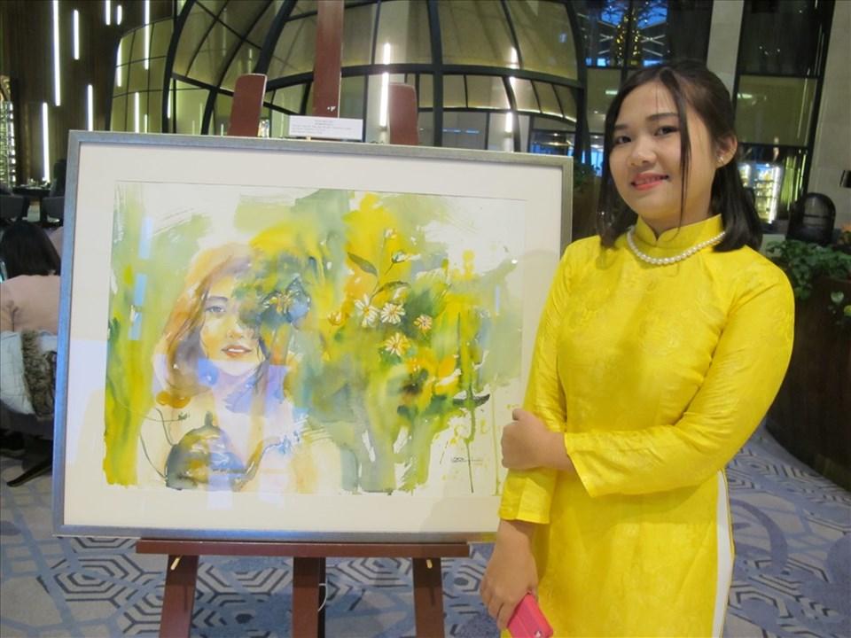 Nữ họa sĩ Lê Ngọc Quỳnh bên tác phẩm tại triển lãm cá nhân đầu tiên của mình. Ảnh: L.Q.V