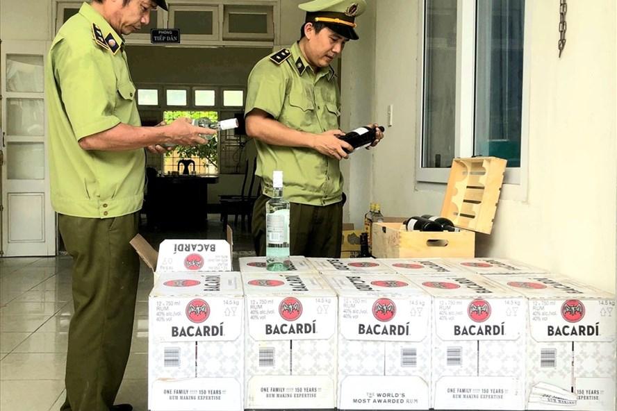Lực lượng QLTT Quảng Bình kiểm tra số rượu lậu vừa bắt giữ. Ảnh: Lê Phi Long