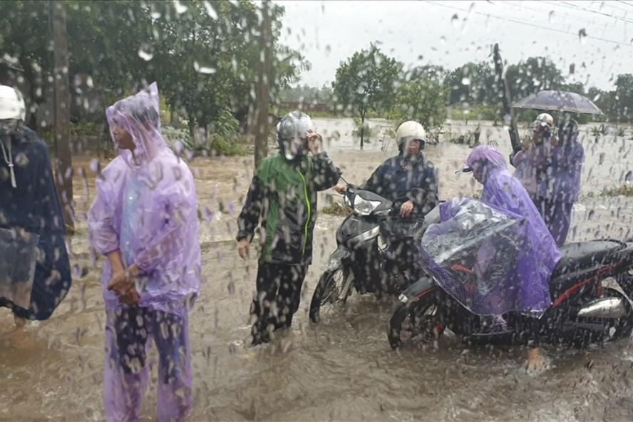 Nhiều người dân đi xe máy gặp khó khăn do bị nước lũ. Ảnh: T.N.D