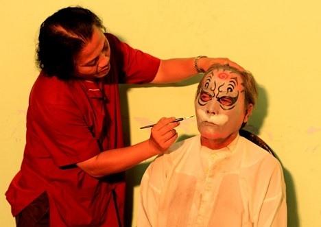 Nghệ nhân La Thanh Hùng vẽ mặt cho diễn viên trong nhà hát.  Ảnh: NVCC