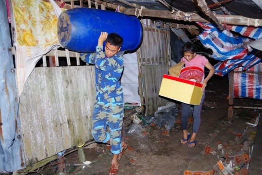 Lực lượng Biên phòng giúp dân di dời nhà tại Thị trấn Sông Đốc, huyện Trần Văn Thời đêm 3.8. Ảnh Lê Khoa
