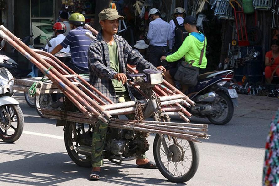 Một xe máy chất đầy giàn giáo công trình bằng sắt. Ảnh: Cao Nguyên